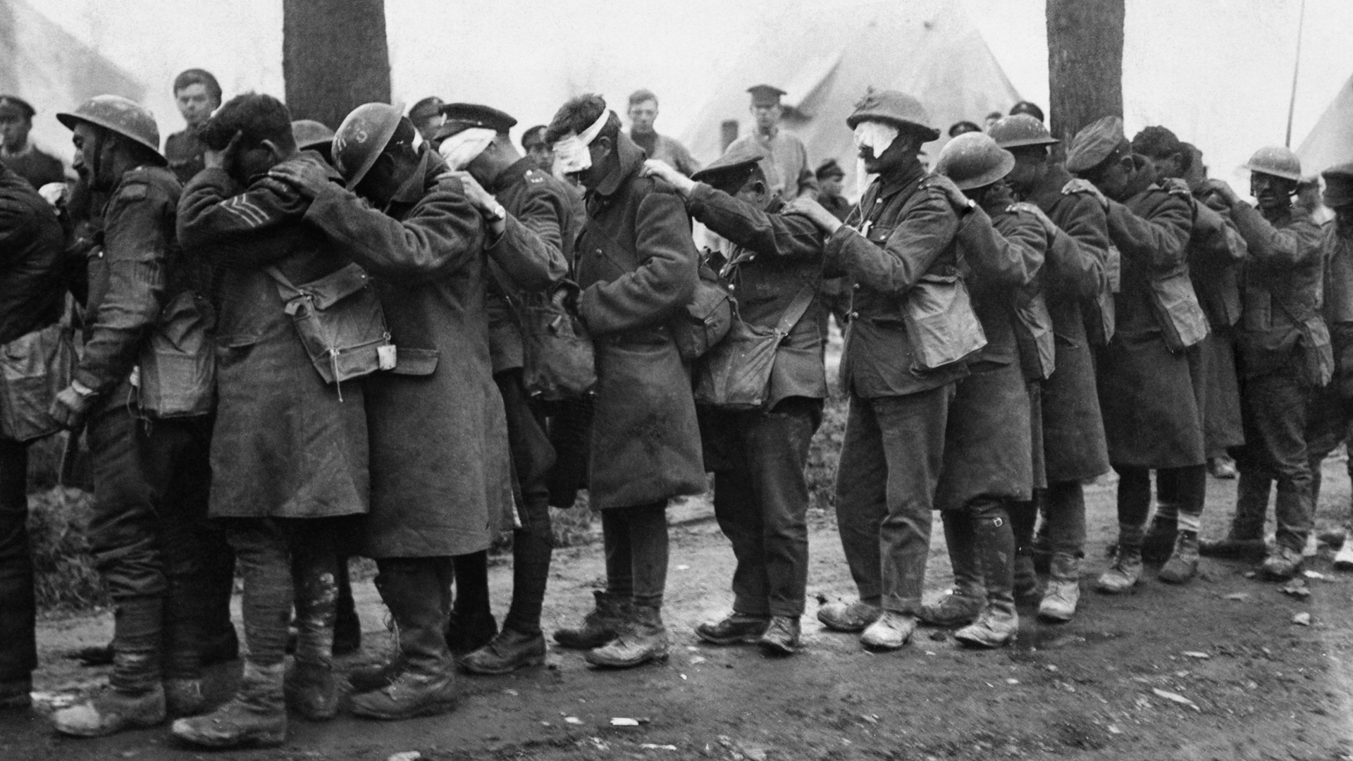 British troops blinded by tear gas waiting outside an Advance Dressing Station, 1918. (Credit: 2nd Lt. T K Aitken/ IWM/Getty Images)