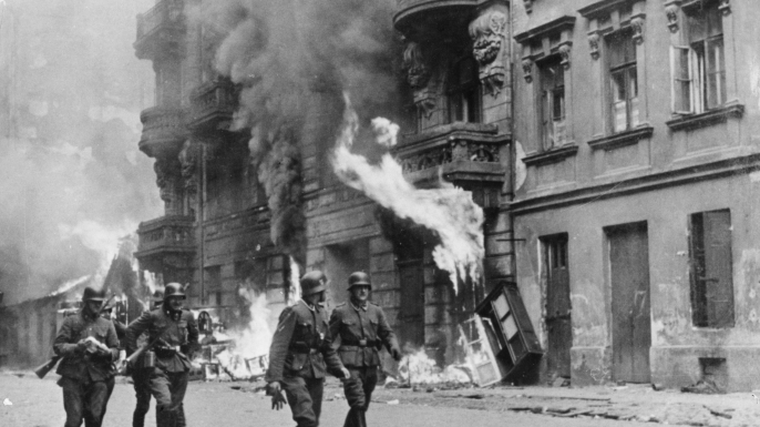 German soldiers walking by fires set in the Warsaw Ghetto, which was burned to the ground after the uprising in 1943. (Credit: Sovfoto/UIG via Getty Images)