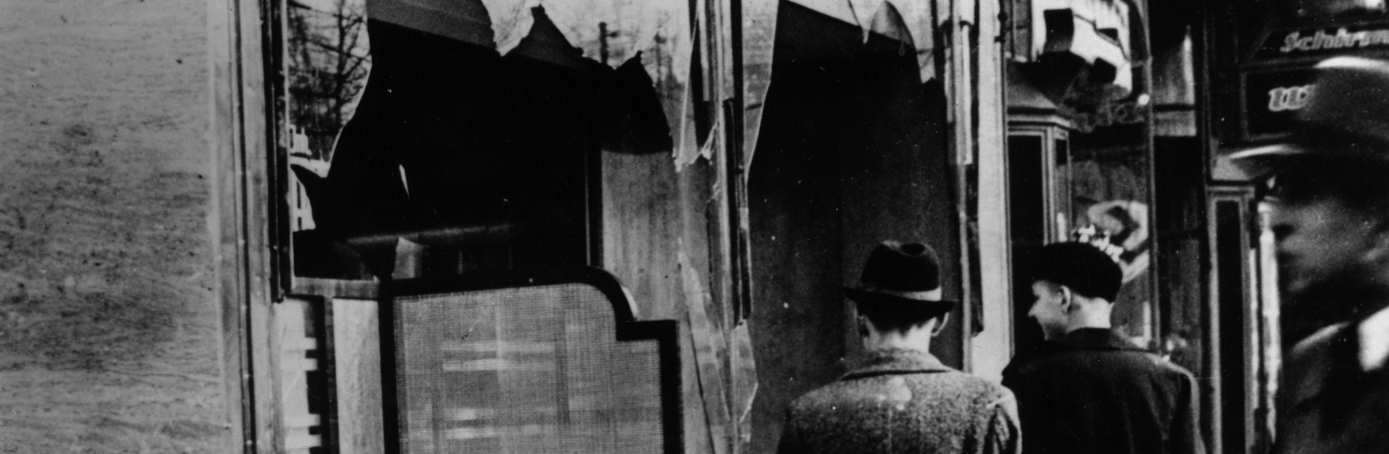 Three onlookers at a smashed Jewish shop window in Berlin following riots of the night of November 9, 1938,  known as Kristallnacht. (Credit: Hulton Archive/Getty Images)
