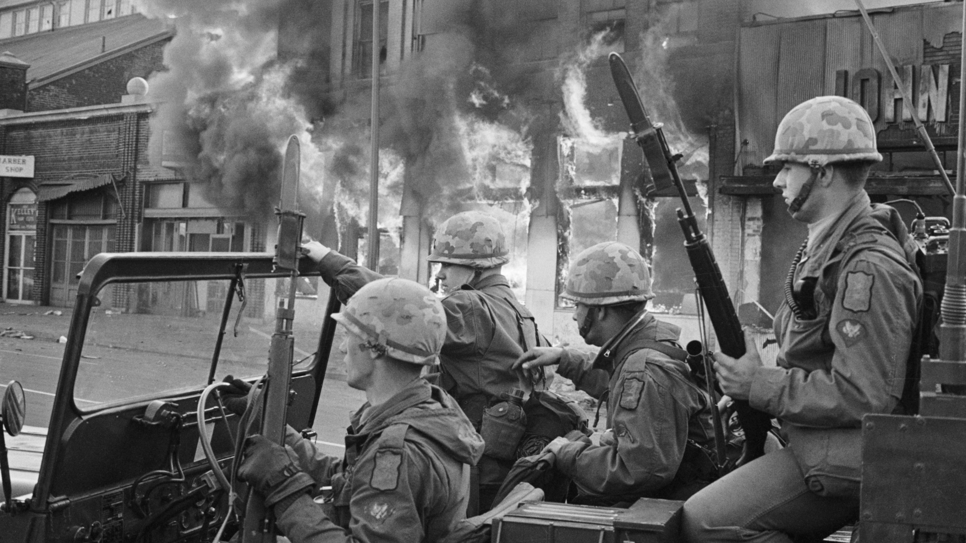 Flames pouring out from a building behind a jeep full of National Guardsmen patrolling the nation's capital as violence erupted after the assassination of Martin Luther King, Jr. (Credit: UPI staff photographer Darryl Heikes)