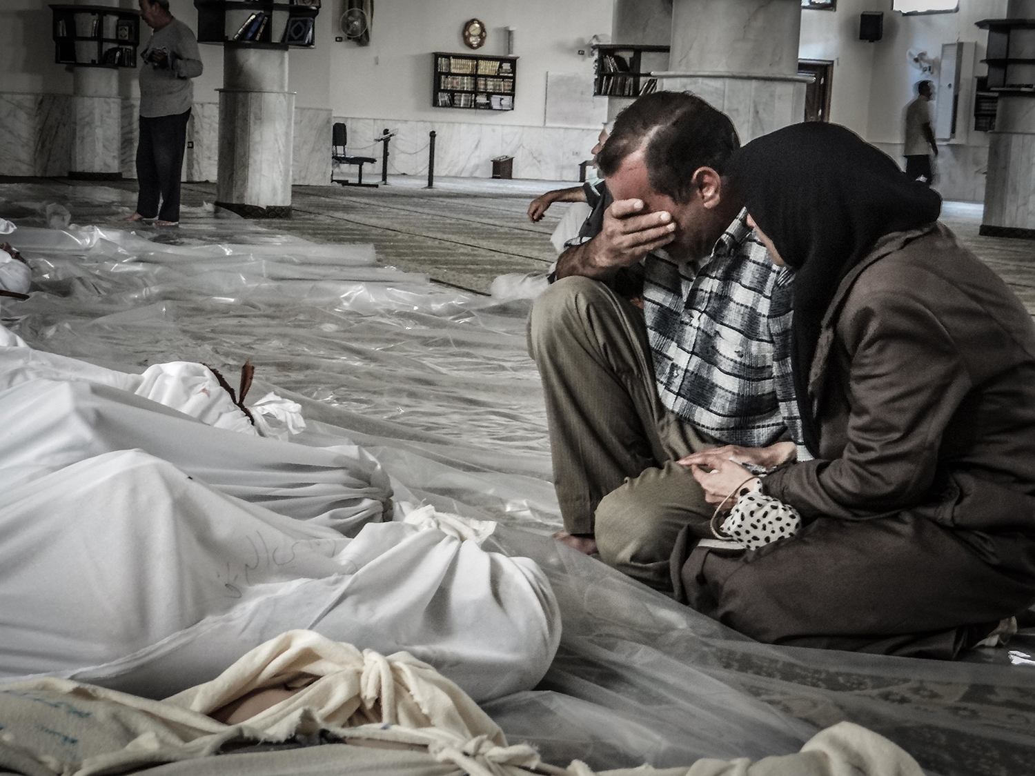 A mother and father weep over their child's body who was killed in a suspected chemical weapons attack on the Damascus suburb of Ghouta, in August 21, 2013. (Credit: NurPhoto/Corbis/Getty Images)