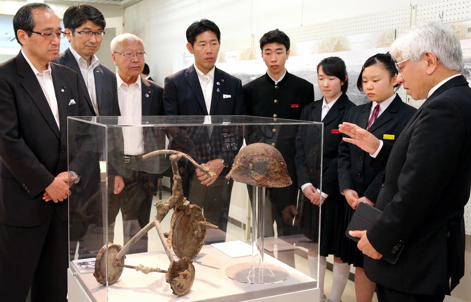Hiroshima Mayor Kazumi Matsui (far left) standing next to Nagasaki Mayor Tomihisa Taue as they look at a display with local students at the Hiroshima-Nagasaki Atomic Bomb Exhibition in 2016. (Credit: The Asahi Shimbun via Getty Images)