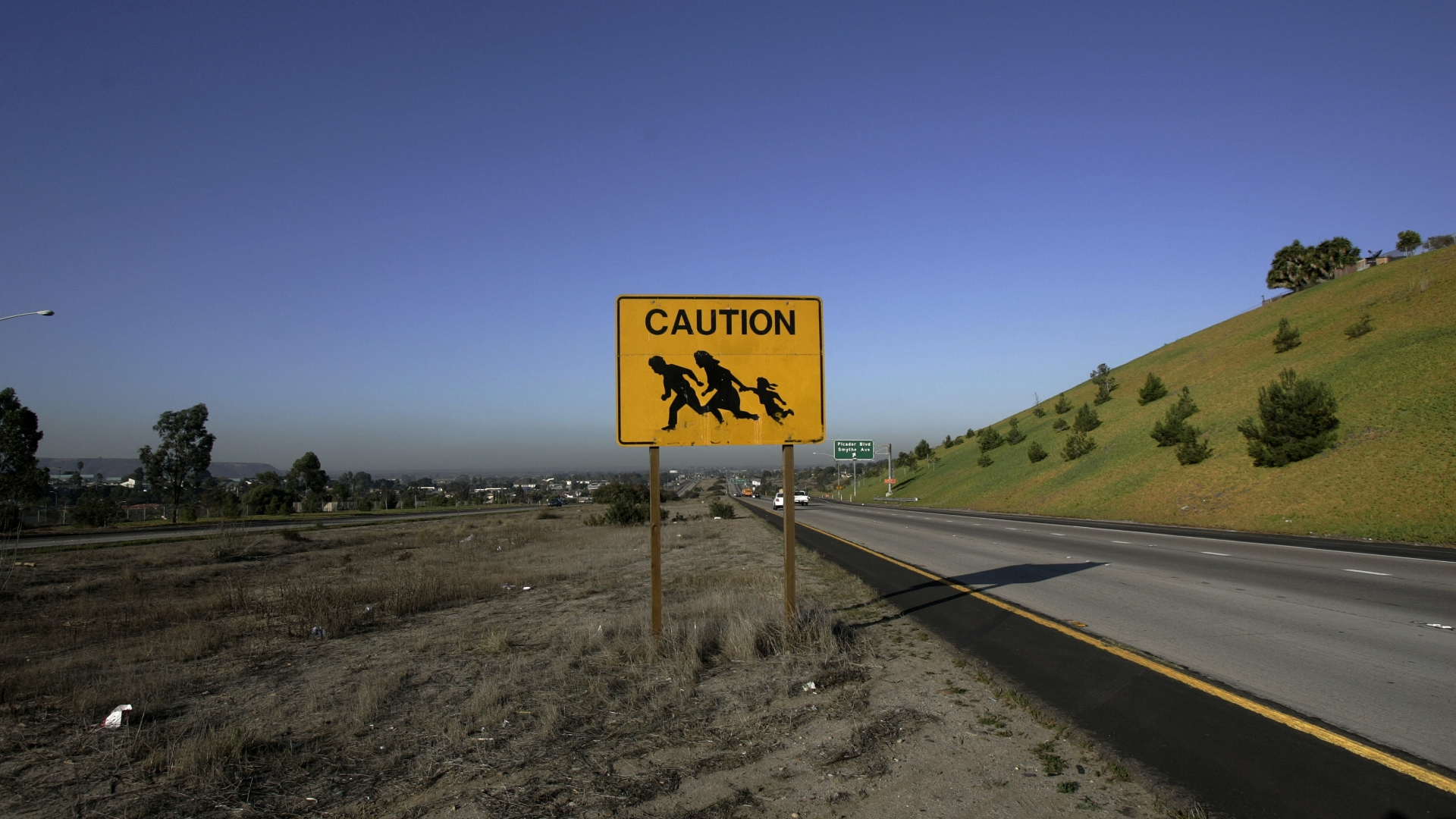 A sign is posted near the US and Mexico border warning drivers of immigrants crossing the freeway in San Ysidro, CA in 2006, just before the signing of the Secure Fence Act. (Credit: Hector Mata/AFP/Getty Images)
