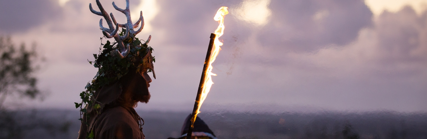 A man representing the Winter King holds a flaming sword as he takes part in a ceremony as they celebrate Samhain at the Glastonbury Dragons Samhain Wild Hunt 2017. (Credit: Matt Cardy/Getty Images)