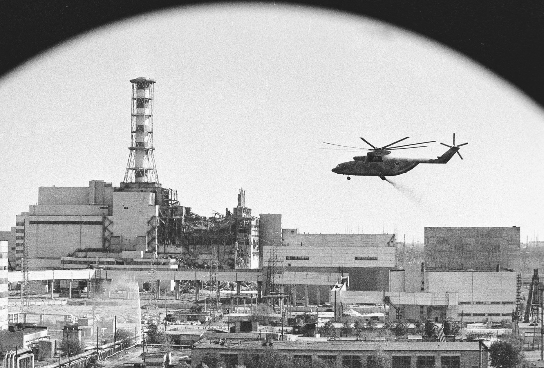 A helicopter 'bomb run' on the damaged Chernobyl reactor (visible in the background). During the first days after the explosion, helicopter pilots dropped thousands of tons of sand, clay, boron and lead into the opening created in the roof of the reactor by the explosion, exposing themselves to extremely high levels of radiation. May 1986 (Credit: Igor Kostin/Sputnik Images)
