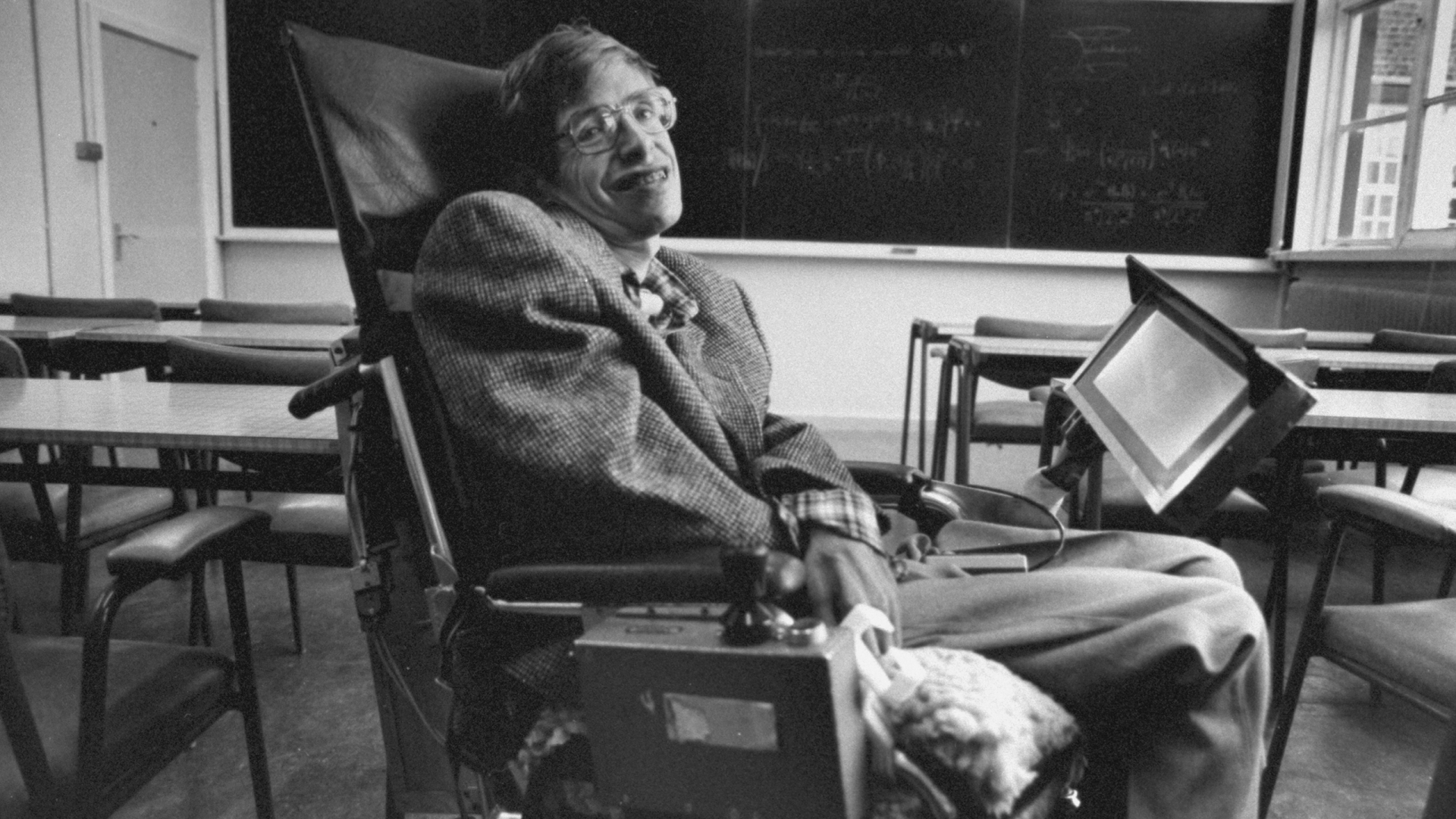 Cambridge Univ. physicist & author Prof. Stephen Hawkings, wheelchair bound due to ALS (amyotrophic lateral sclerosis, aka Lou Gehrig's disease), inside a lecture hall w. math equations on blackboard behind him.  (Photo by Terry Smith/The LIFE Images Collection/Getty Images)