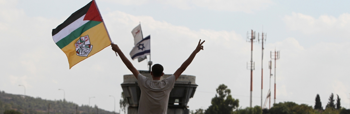 A Palestinian protester waves the Fatah and the Palestinian flag near a Israeli army watchtower during a weekly demonstration against the confiscation of Palestinian land by Israel in the central West Bank village of Nabi Saleh near Ramallah on October 5, 2012. (Credit: Abbas Momani/AFP/GettyImages)