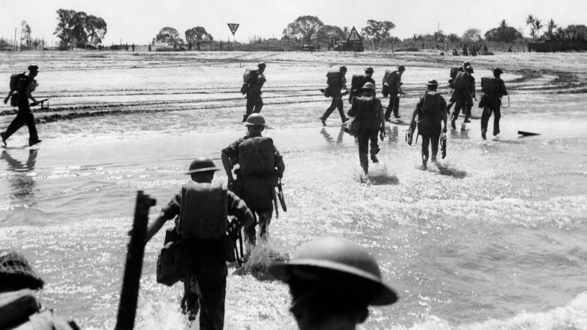 Allied troops run ashore after the amphibious assault on Japanese-held Ramree Island. (Credit: PA Images/Getty Images)