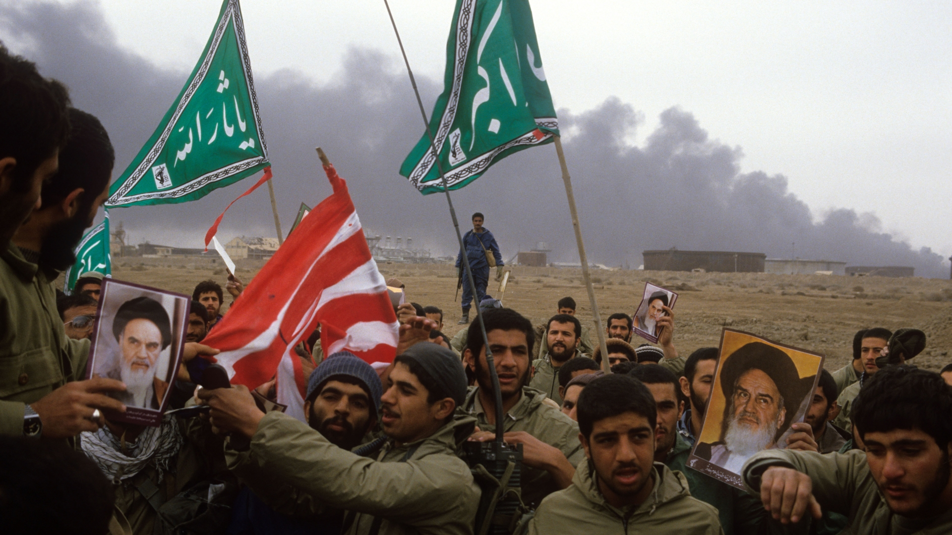 Iran's Revolutionary Guards preparing to burn an American flag on the al-Fao Peninsula after it was recaptured by Iranian forces from the Iraqi army during the Iran-Iraq War, 1986. The combatants hold up photographs of Ayatollah Khomeini, along with green flags reading 'Allah Akbar'  which translates to 'God is Great'. (Credit: Kaveh Kazemi/Getty Images)