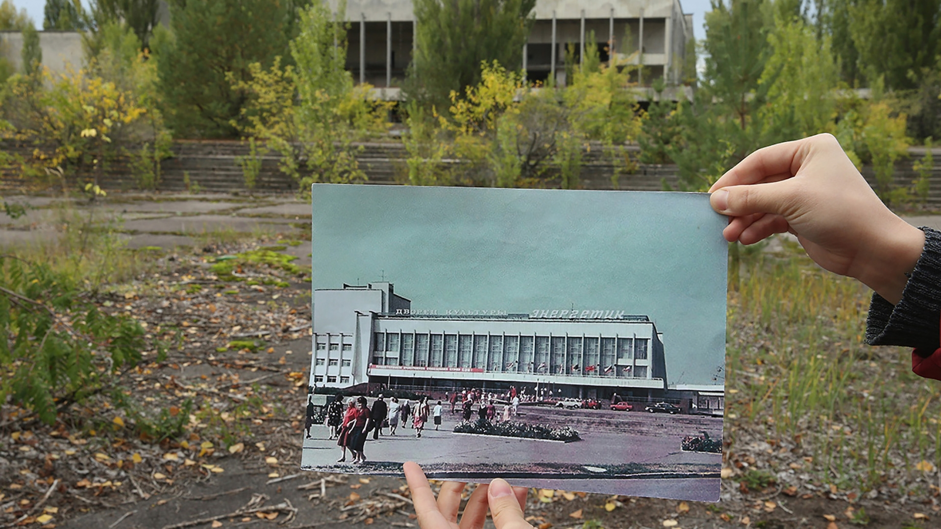 A person holds up a photo showing the city of Prypiat's main square and the 'Energetik' cultural center before the 1986 Chernobyl nuclear disaster, against the same site, now abandoned and overgrown with trees, 2015. (Credit: Sean Gallup/Getty Images)