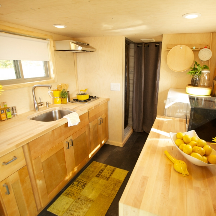 A Bright, Sunny Tiny House Kitchen With Natural Woods And